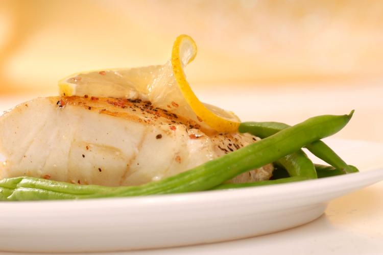 Mahimahi on a plate with lemon garnish and green beans.
