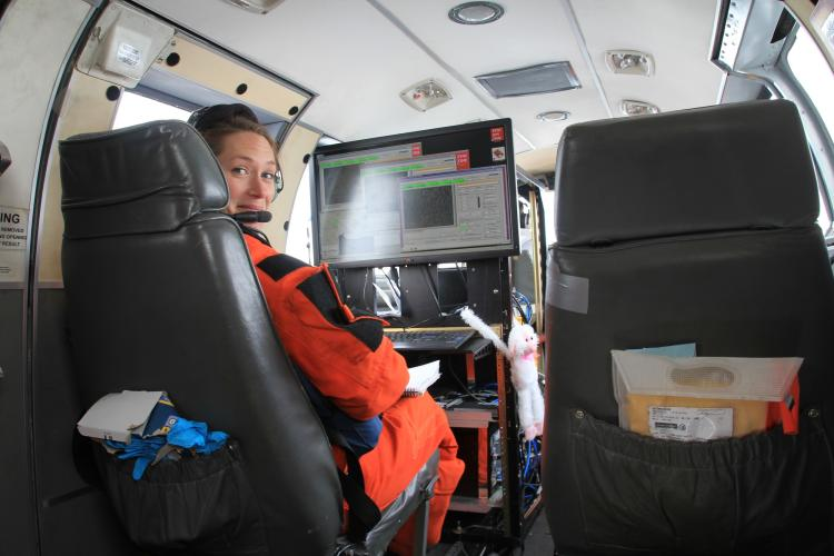 Photo of Cynthia Christman in front of a computer workstation on board an airplane.