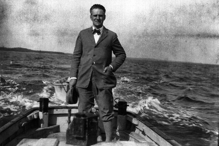 Paul Galtsoff stands at back of a small boat underway, 1932