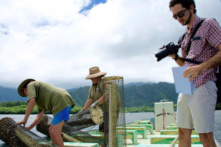 Science writer taking notes and pictures of two workers from Kualoa Ranch's Moli`i fishpond offloading oyster-filled baskets from a boat.