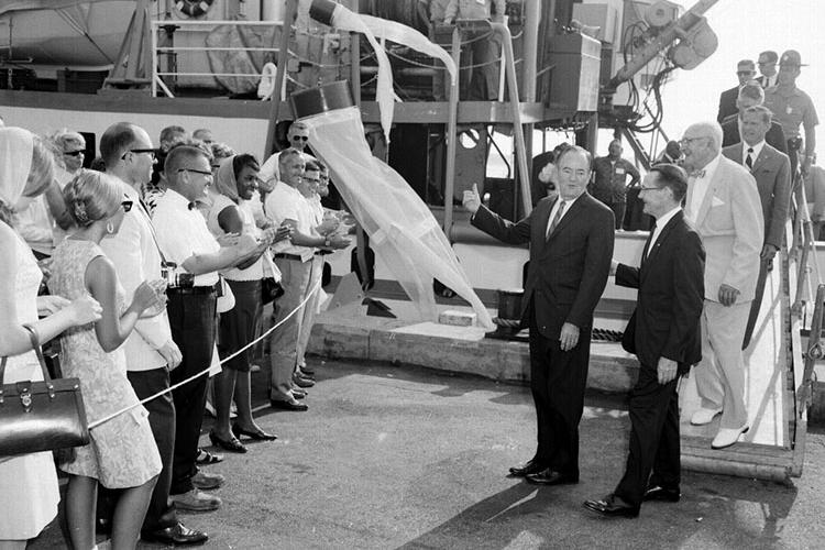 Crowd of people at left applaud as Vice President Hubert Humphrey approaches after a visit to the R/V Albatross IV in the background. Next to Humphrey is Woods Hole Lab director Herbert Graham, followed by scientist Paul Galtoff and others coming down the gangway of the ship.  A bongo plankton net hangs off the side of the ship