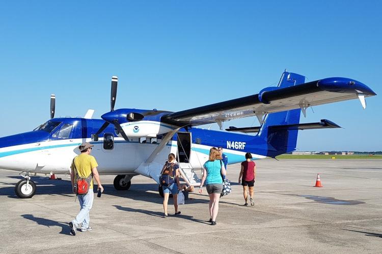 Observers walking to NOAA Twin Otter plane on the tarmac.