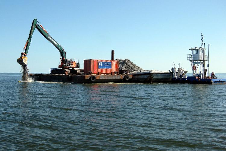 A backhoe on a barge dumps limestone into the water
