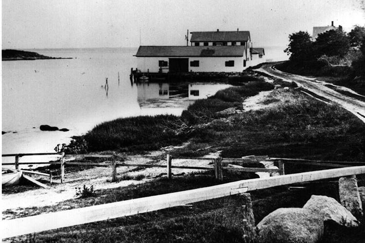 a two-story building on the edge of a harbor set off from the main road by a dirt road and wooden fence.