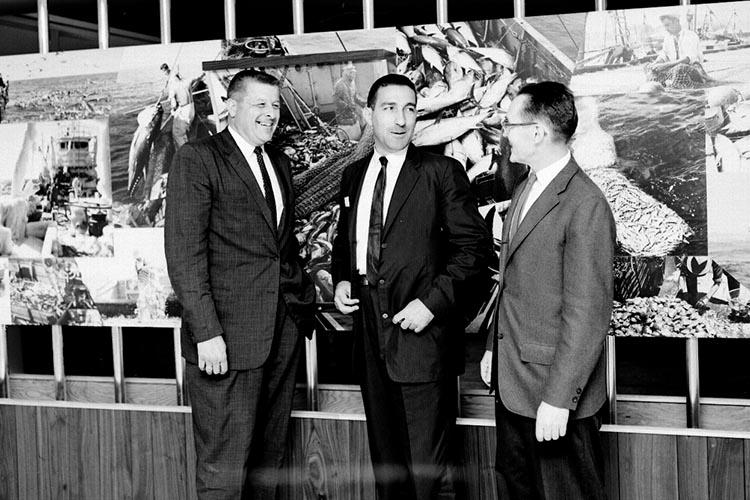 three men stand in front of a wall of photos in the Woods Hole Aquarium talking and smiling. Secretary Udall is at center. Jack x is at left and Woods Hole Lab director Herbert Graham is at right.