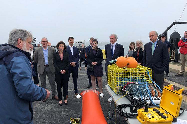 Man stands in a parking lot next to a table of prototype equipment on the dock explaining its use to a line of government officials and other invited guests standing left to right including Northeast Fisheries Science Center director Jon Hare, Secretary Gina Raimondo, Senator Edward Markey and Congressman William Keating.