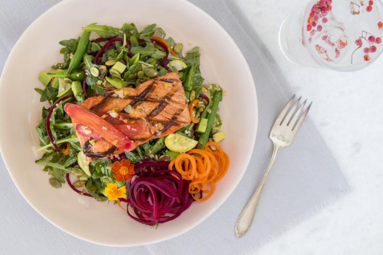 Plate of Alaska salmon and veggie salad on a table.