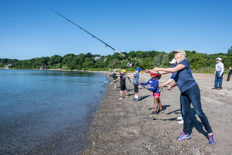 Janet Coit fishing at a youth fishing camp