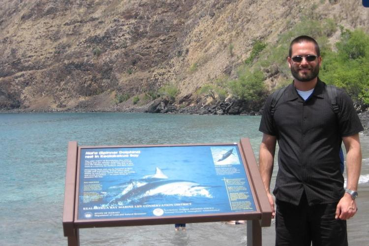 Trevor in Kealakekua Bay on the Big Island of Hawaii next to a sign he helped design to teach visitors about Hawaiian spinner dolphins and how to view them safely and responsibly.