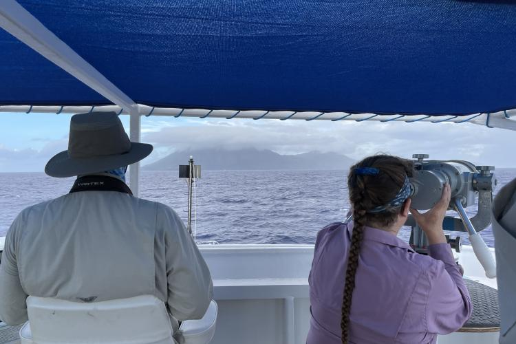 A seabird observer and a cetacean observer scan the water with handheld and big eye binoculars, respectively.