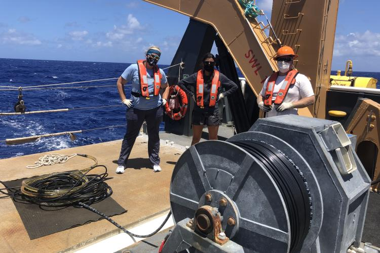 Three acousticians on the aft deck with the hydraulic winch and towed hydrophone array coiled on the deck in the foreground.