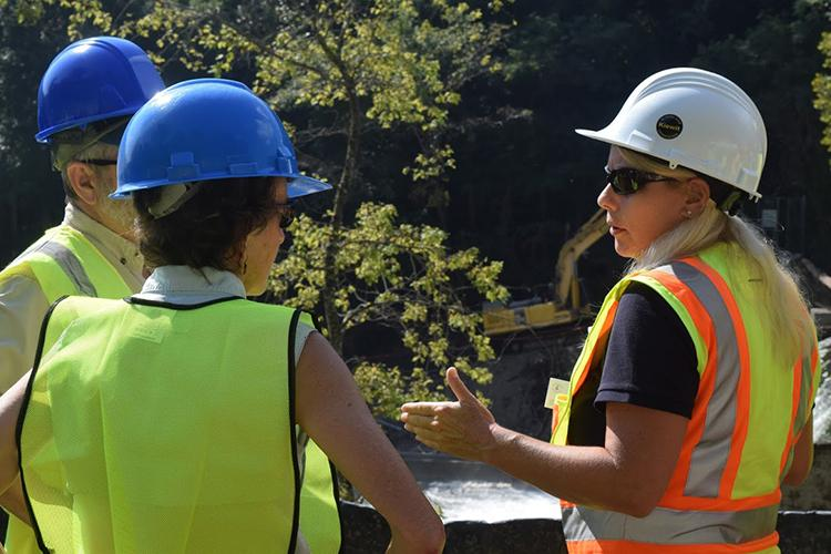 Three people in hard hats and safety vests standing near a river
