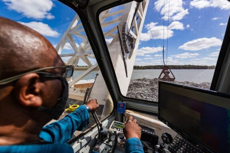 A view from inside a crane working to move oyster shell from a barge.