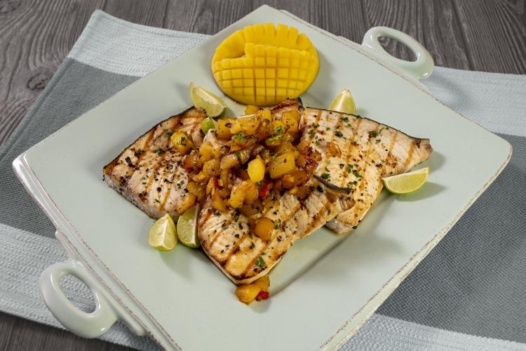 Grilled swordfish filets with mango chutney on a plate.