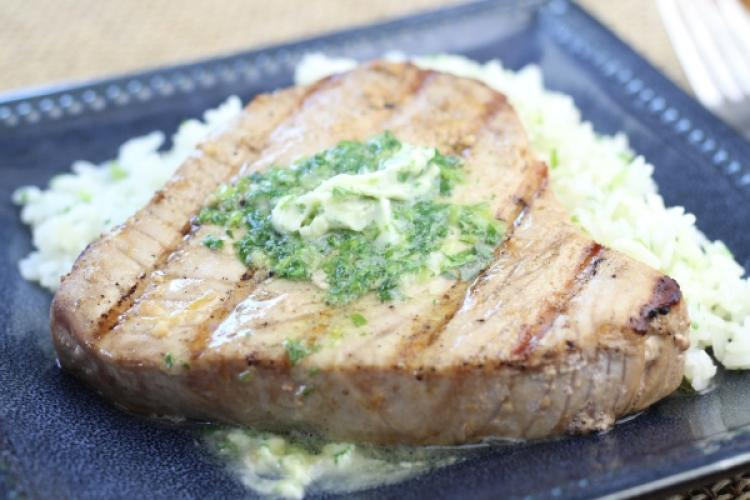 Grilled tuna with melted herb butter on top.