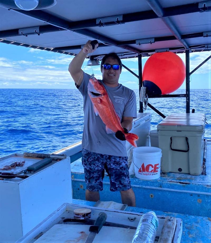 Captain Layne Nakagawa of the F/V Naomi K holding an ehu. Photo courtesy of Pacific Islands Fisheries Group/Fishing Vessel Naomi K.