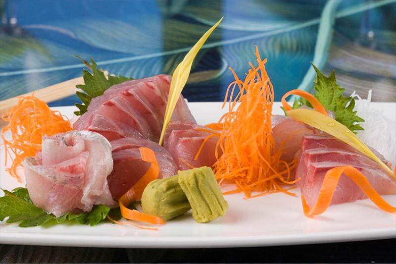 Thinly sliced cut fish on a plate garnished with vegetables and wasabi.