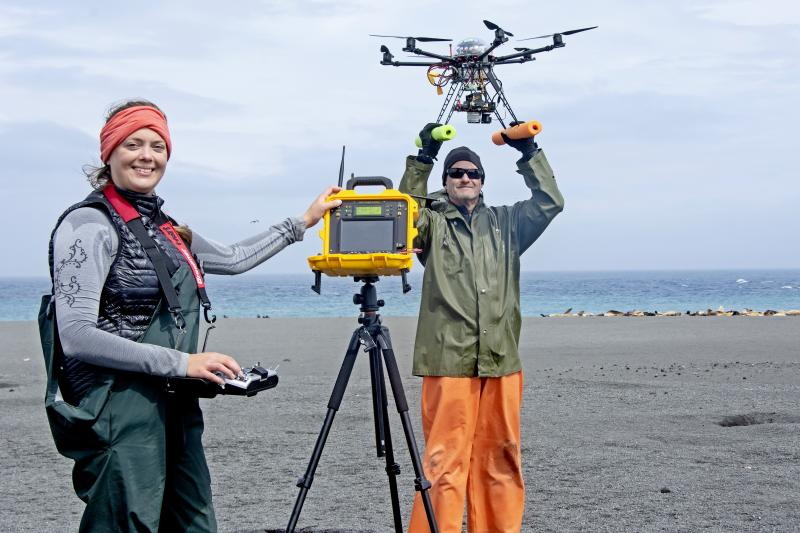 Photo of Katie Sweeney, holding a remote control console, and Brian Fadely, holding a drone, on a Bogoslof Island beach..