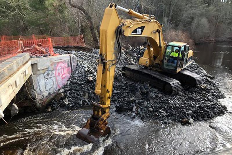 An excavator demolishing a dam.