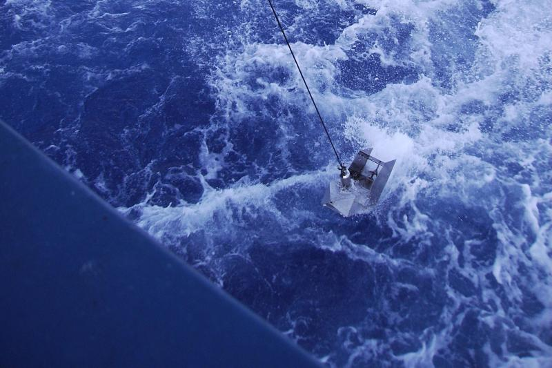A continuous plankton recorder is lowered into the water for towing behind a commercial vessel.