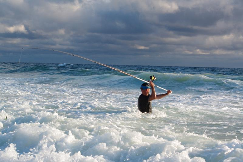 A recreational angler casts a line in the surf.