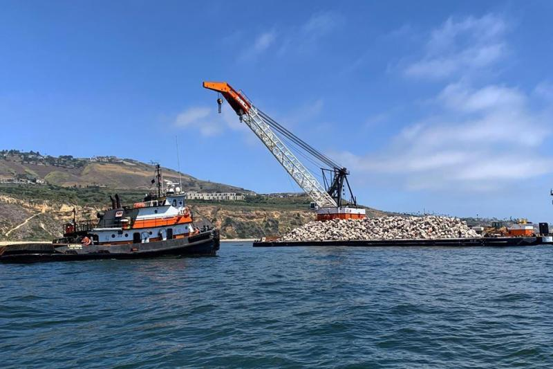 A tug boat approaching large barge with a pile of boulders off the California coast.