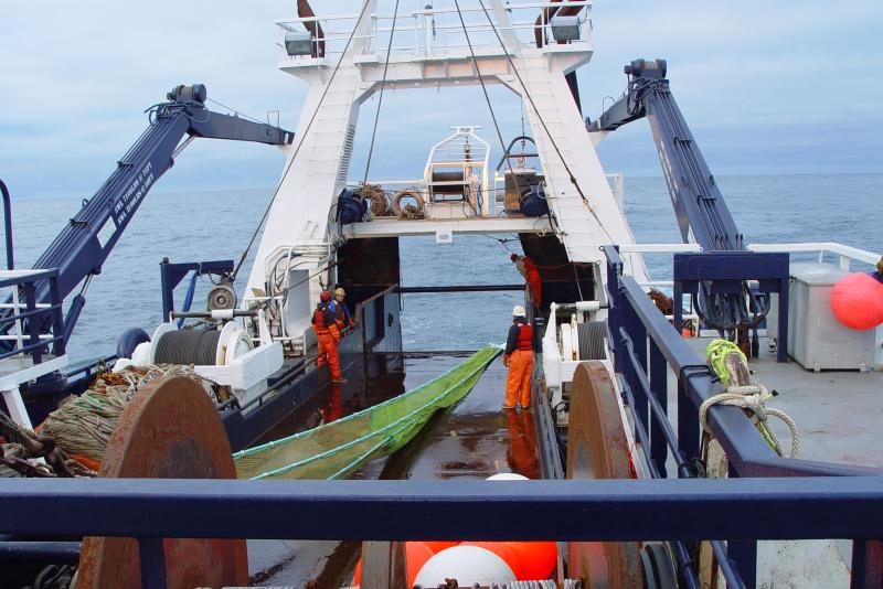 Photo of workers on a boat deck with a surface trawl net.