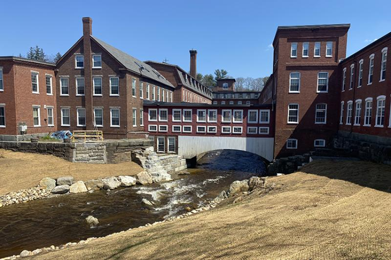 A river runs under a bridge and between several buildings