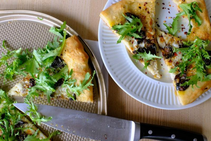 Slices of garlic chili oil and smoked oyster pizza on baking pan and a white plate, topped with fresh greens.