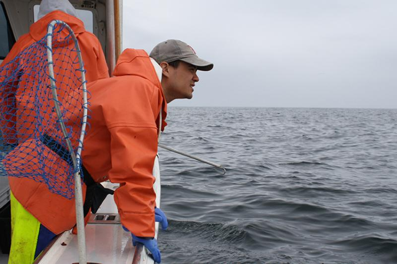 Researcher standing on deck of ship.