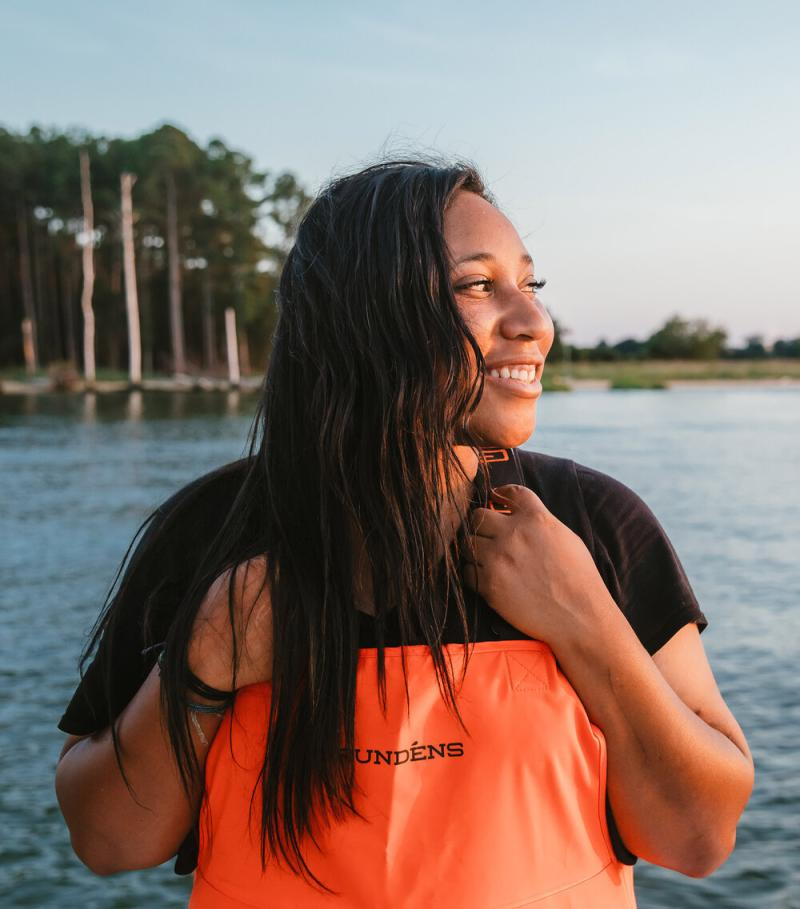 A photo of Imani Black wearing waders and looking out across the water.