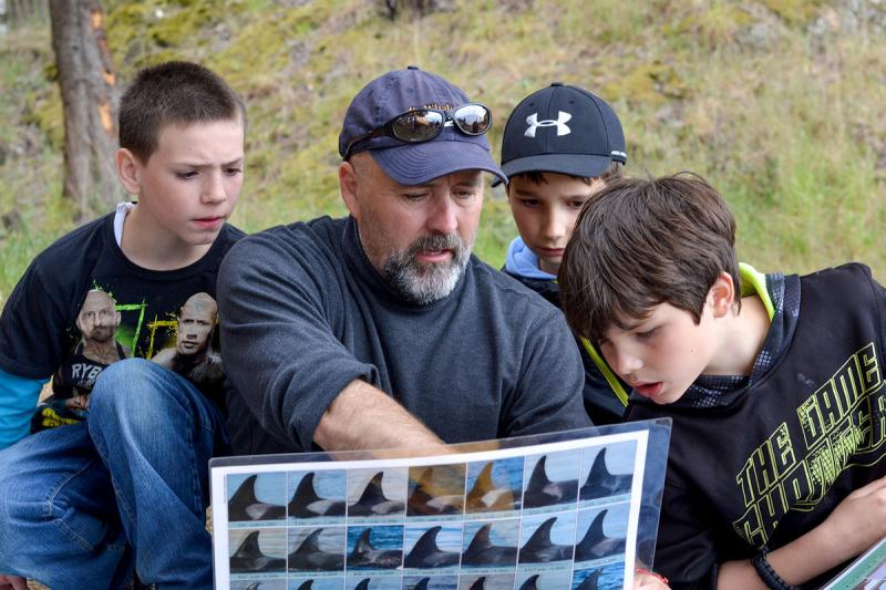 Jeff Hogan hold a post showing identifying features of killer whales