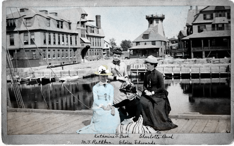 Four women, including Mary Jane Rathbun, sitting on a Fish Commission wharf dock in Woods Hole, Massachusetts.
