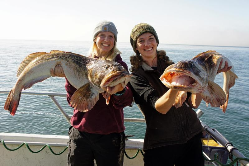two women each holding a lingcod