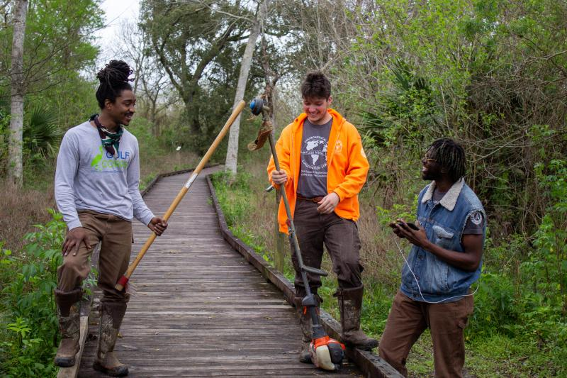 Three young people standing on a boardwalk in the woods with landscaping equipment.