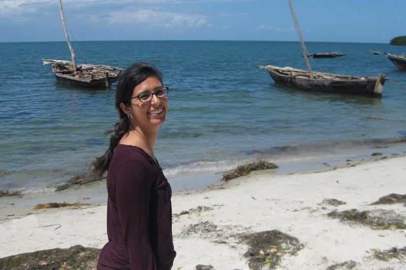 Nicole Naar standing on a tropical beach in Tanzania, with small fishing boats floating on the water close by.