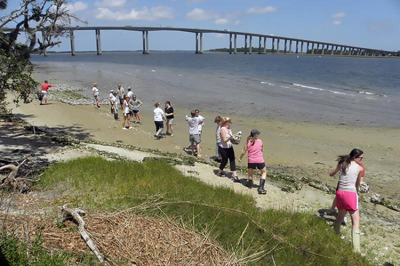 Volunteers standing along the shoreline and passing bags of oysters down the line to help construct a living shoreline