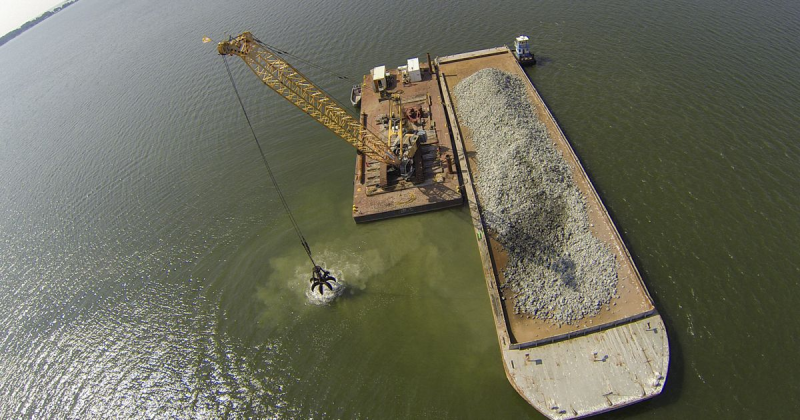 A crane moves material to build an oyster reef from a barge into the Piankatank River.