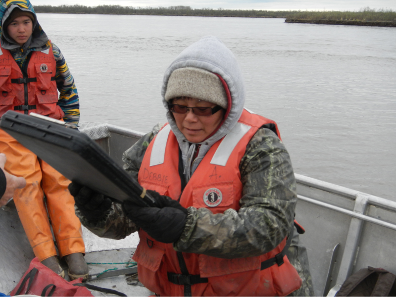 Photo of two technicians in a boat recording information on a tablet.
