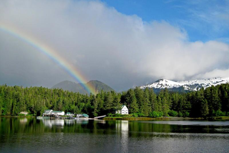 Photo of the Little Port Walter Marine Research Station, with a rainbow and mountains in the background, viewed from the water.