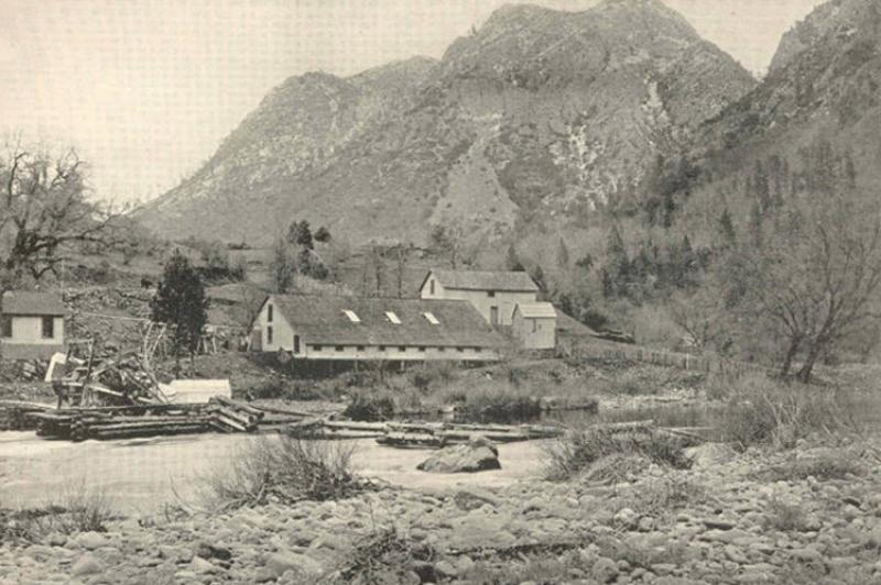 Wooden buildings of Baird Station, with McCloud River in the foreground, mountains behind