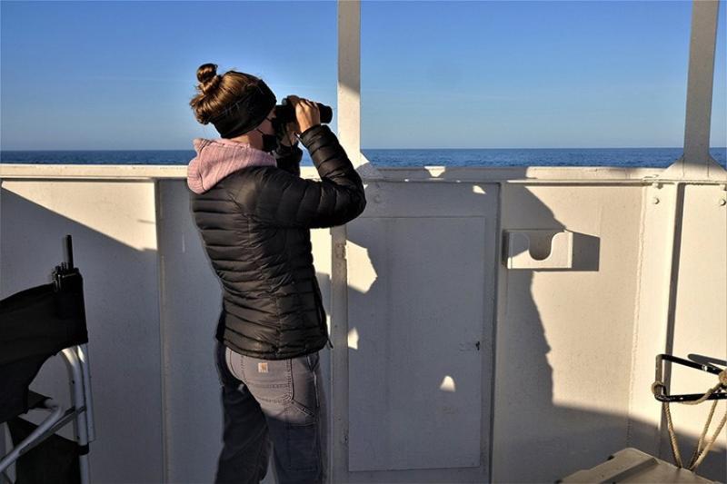 Seabird observer with binoculars on the flying bridge of the Gordon Gunter