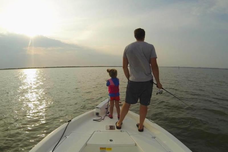 Man and child fishing off boat