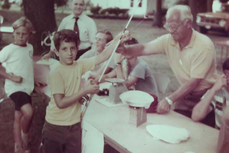 A young boy gives a fishing rod to an older man across a table.