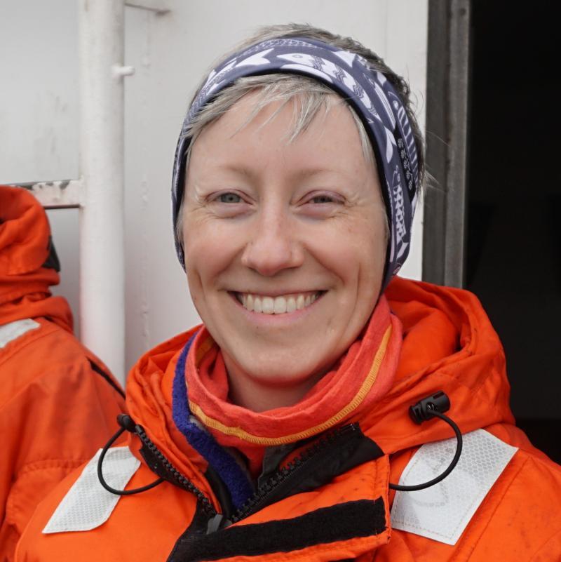 Photo of Katie Luxa wearing an orange flight suit.