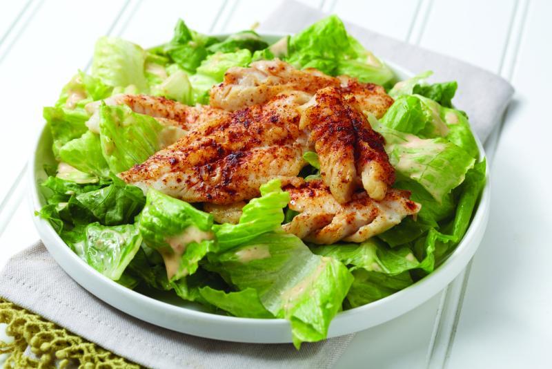 Plate of pollock Caesar salad on a table.
