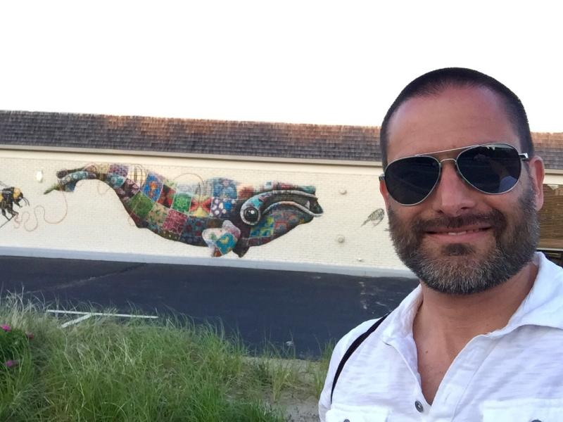 Trevor in Provincetown, Massachusetts in front of a North Atlantic right whale mural painted by wildlife conservation artist Louis Masai to raise awareness about the endangered species.