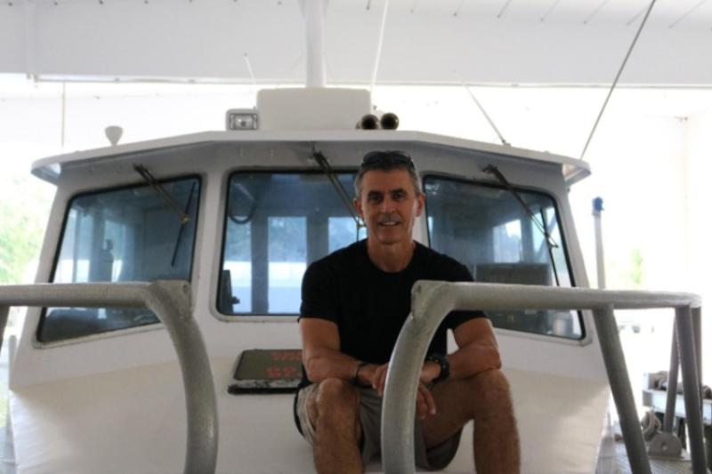 Enric Cortés sitting on the deck of a vessel preparing for fieldwork.