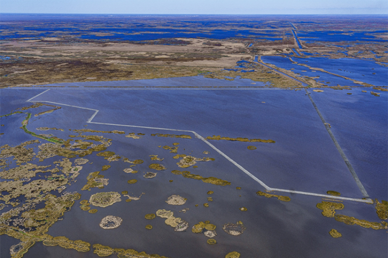 Aerial image of wetlands, open water, and containment dikes