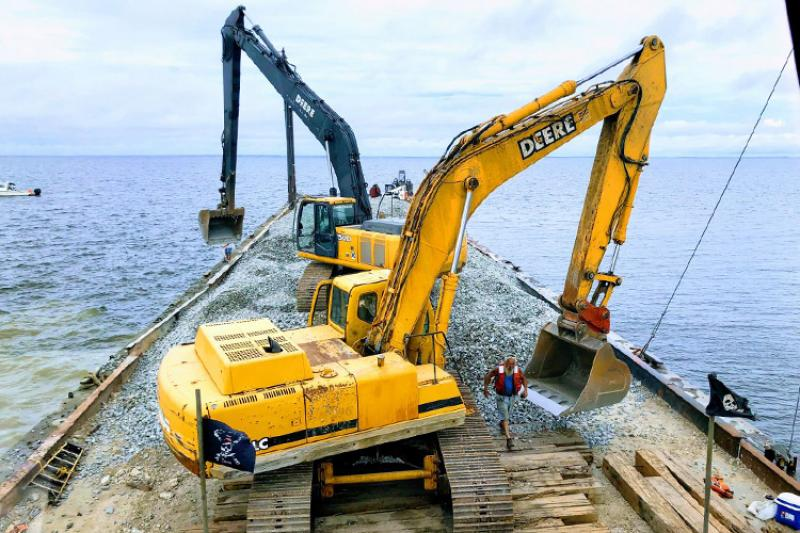 Two excavators on a barge floating in the water